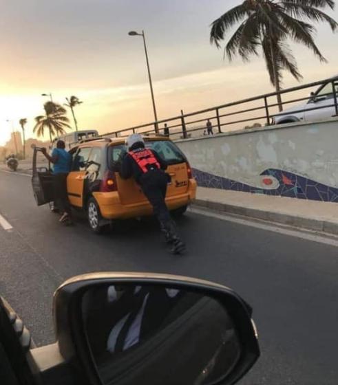 Arrêt sur image: un motard de la Police qui aide un chauffeur de taxi en panne.